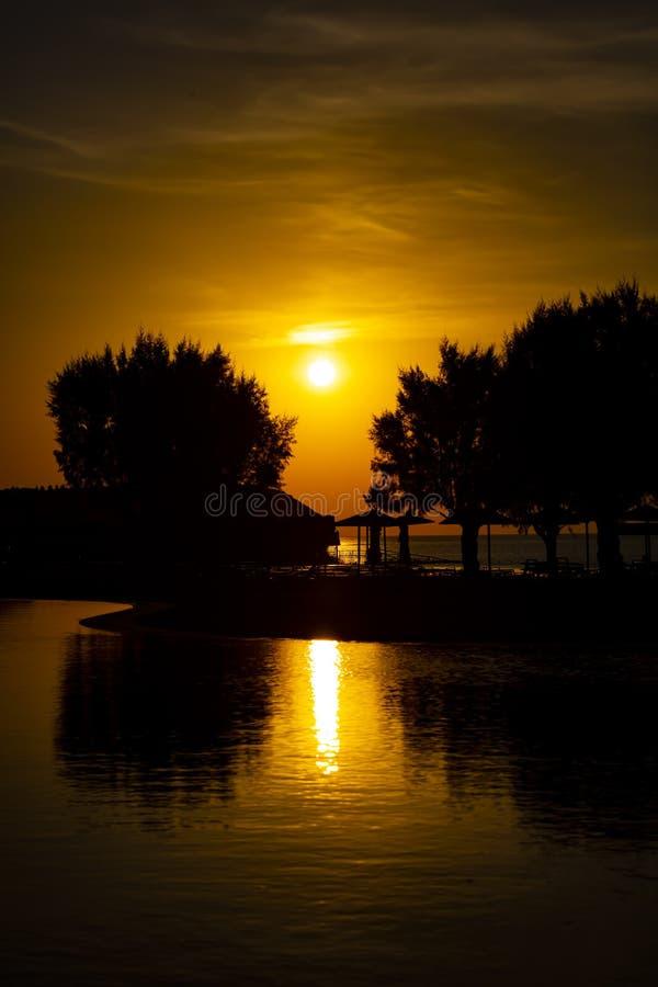 Bella siluetta del sole che aumenta in Rodi, Grecia L'immagine mostra i parasoli e gli alberi di bambù fotografia stock libera da diritti