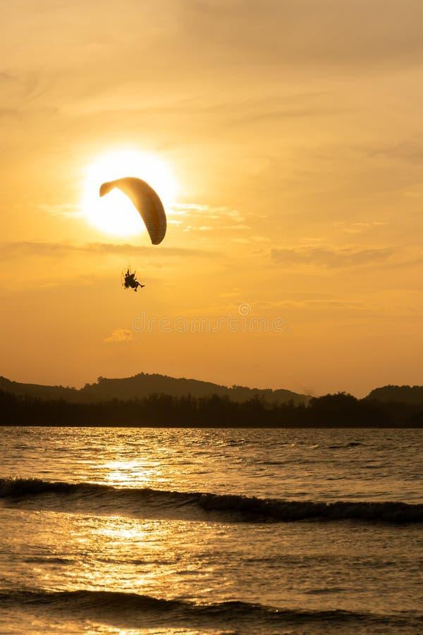 Bella siluetta del volo dell'aliante nel cielo del tramonto sulla spiaggia fotografia stock