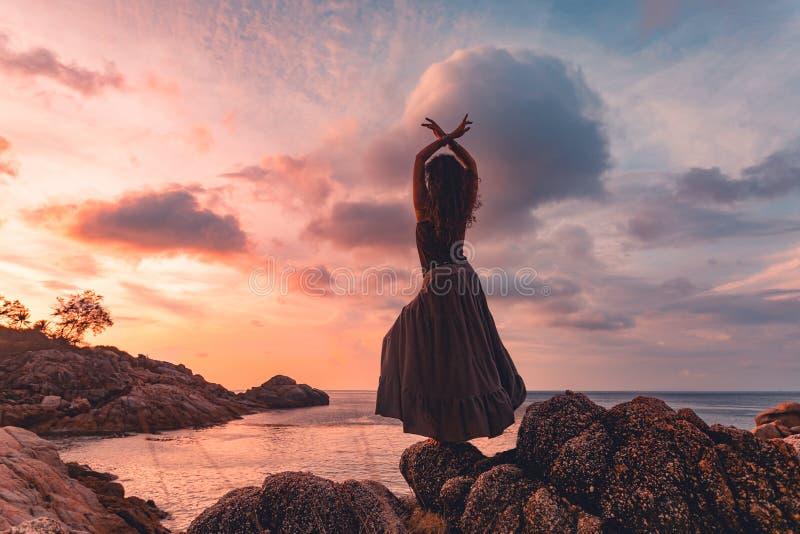 Bella siluetta della giovane donna sul tramonto fotografia stock