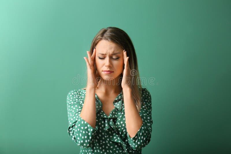Bella sofferenza della giovane donna dall'emicrania sul fondo di colore fotografia stock