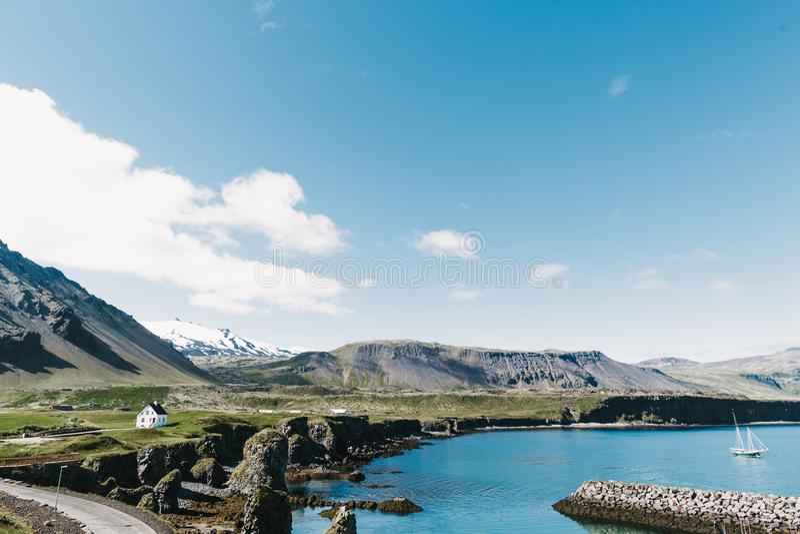 bella spiaggia con l'yacht di galleggiamento su acqua, sulla strada, sulle montagne rocciose e sulle case sulla riva nel gatklett fotografie stock