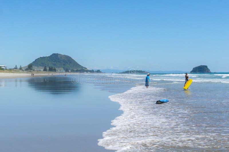 Bella spiaggia dell'oceano di vista lunga con la gente che gode delle attività della spiaggia e del tempo immagine stock libera da diritti