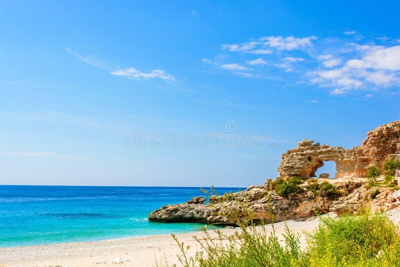 Bella spiaggia sabbiosa con una scogliera mare ionico in Dhermi, Albania immagini stock libere da diritti