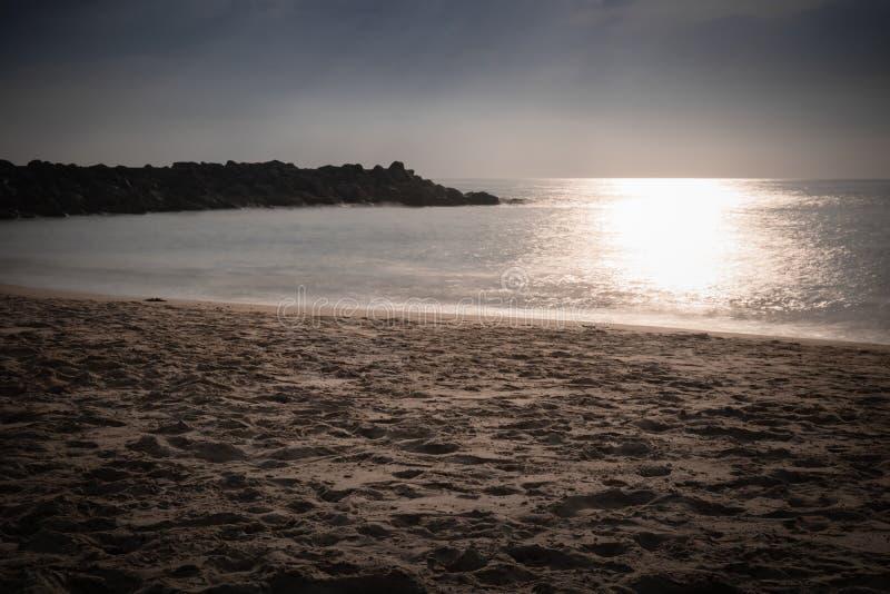 Bella spiaggia scenica sabbiosa nel tramonto, con il frangiflutti roccioso nell'esposizione lunga in paese basco, la Francia, fon fotografia stock