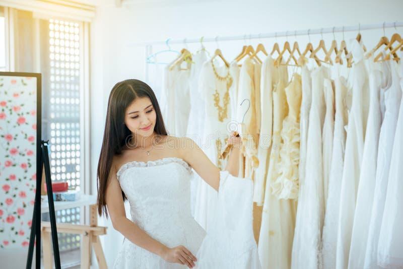 Bella sposa asiatica della donna che prova sul vestito da sposa bianco nella sala fotografie stock