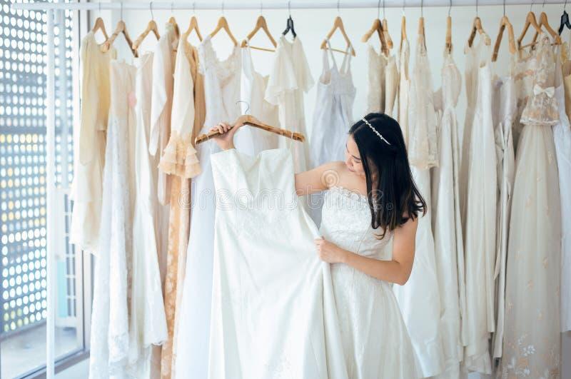 Bella sposa asiatica della donna che prova sul vestito da sposa, felice e sul sorridere fotografia stock libera da diritti