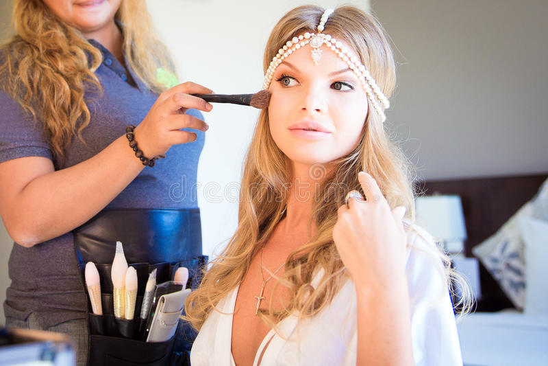 Bella sposa bionda che fa trucco nel suo giorno delle nozze vicino al mirro fotografia stock libera da diritti