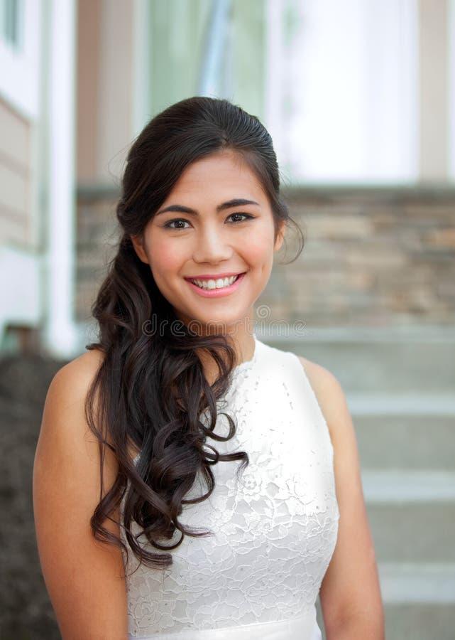 Bella sposa biraziale in vestito da sposa bianco dal pizzo, sorridente immagine stock libera da diritti