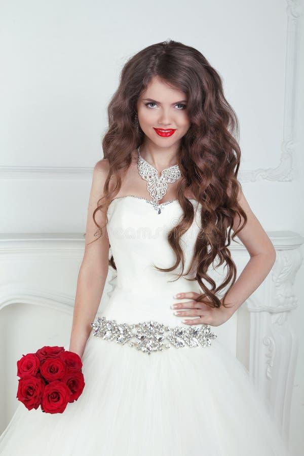 Bella sposa castana felice con capelli ondulati lunghi che disegnano holdi fotografia stock