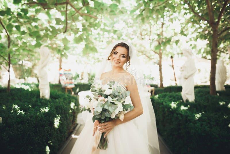 Bella sposa castana nel mazzo bianco elegante della tenuta del vestito che posa gli alberi ordinati fotografia stock