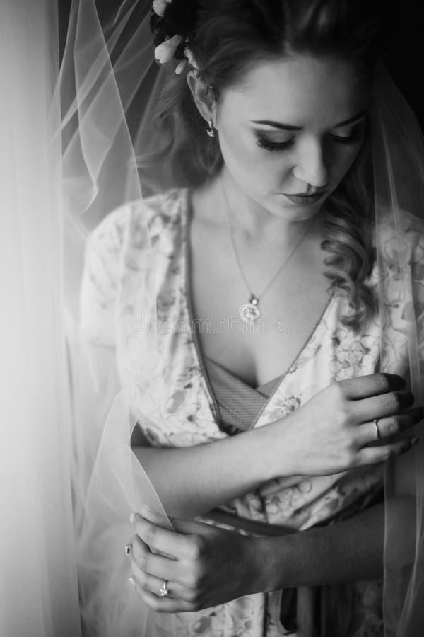 Bella sposa che guarda dalla finestra, preparati di nozze di mattina fotografie stock