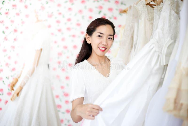 Bella sposa che si veste dal suo migliore amico nel suo giorno delle nozze e che sceglie un vestito da sposa nel negozio e nel ne immagini stock libere da diritti