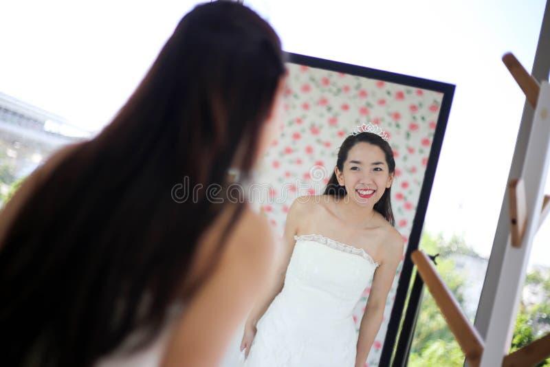 Bella sposa che si veste dal suo migliore amico nel suo giorno delle nozze e che sceglie un vestito da sposa nel negozio e nel ne fotografia stock