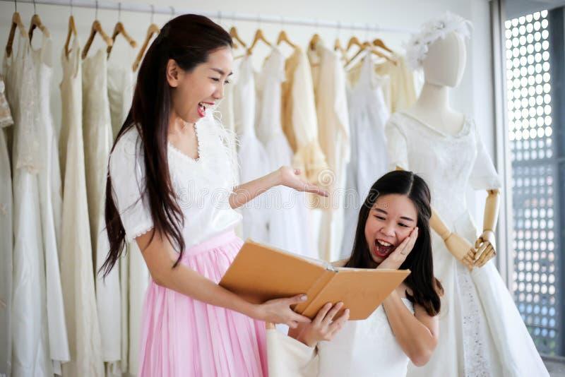 Bella sposa che si veste dal suo migliore amico nel suo giorno delle nozze e che sceglie un vestito da sposa nel negozio e nel ne fotografia stock libera da diritti