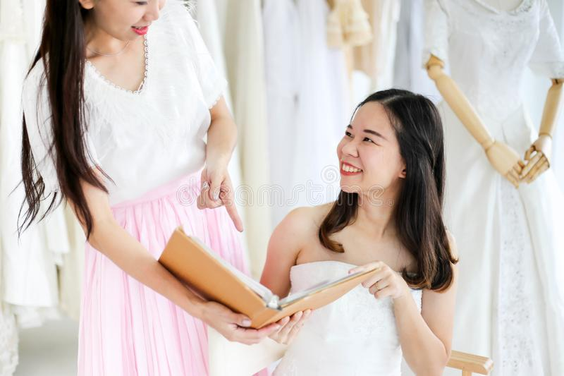 Bella sposa che si veste dal suo migliore amico nel suo giorno delle nozze e che sceglie un vestito da sposa nel negozio e nel ne immagine stock libera da diritti