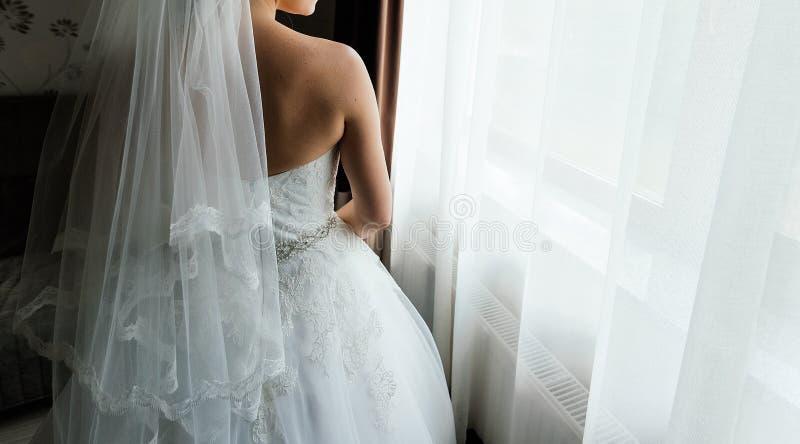 Bella sposa che sta alla finestra, vista posteriore fotografia stock libera da diritti