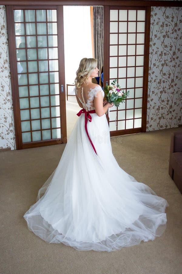 Bella sposa con capelli ed il vestito da sposa dai vestiti di trucco con allacciamento alla parte posteriore e un mazzo di nozze  fotografia stock