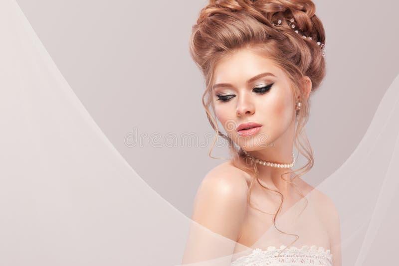 Bella sposa con l'acconciatura di nozze di modo - su fondo grigio Ritratto del primo piano di giovane sposa splendida nozze fotografie stock