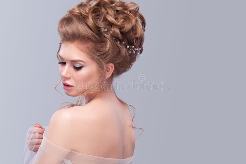 Bella sposa con l'acconciatura di nozze di modo - su fondo grigio Ritratto del primo piano di giovane sposa splendida nozze Sho d fotografie stock libere da diritti