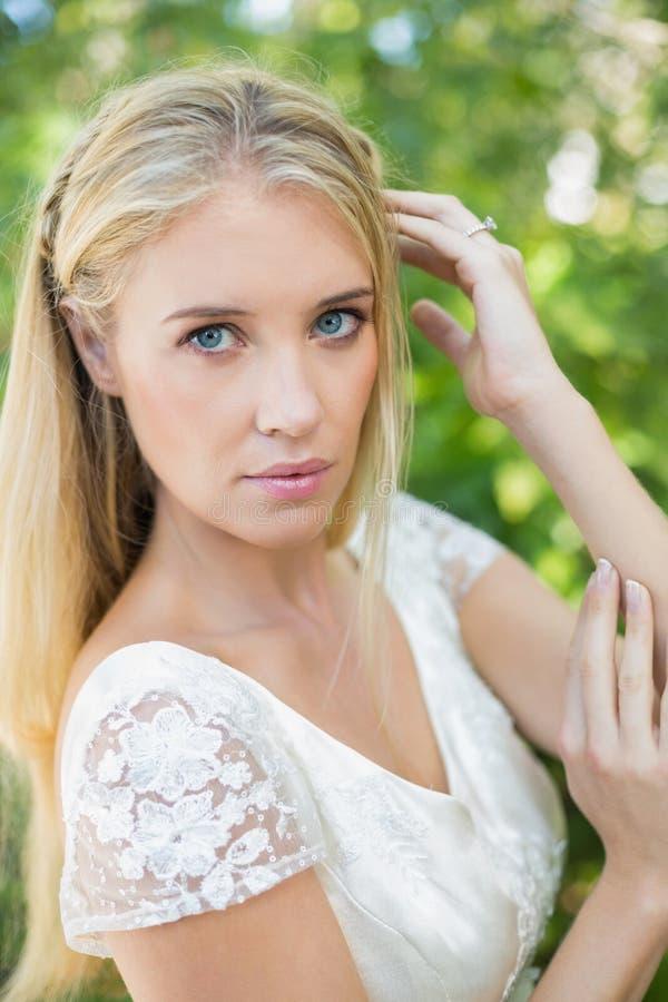 Bella sposa contenta che tocca i suoi capelli che esaminano macchina fotografica immagine stock