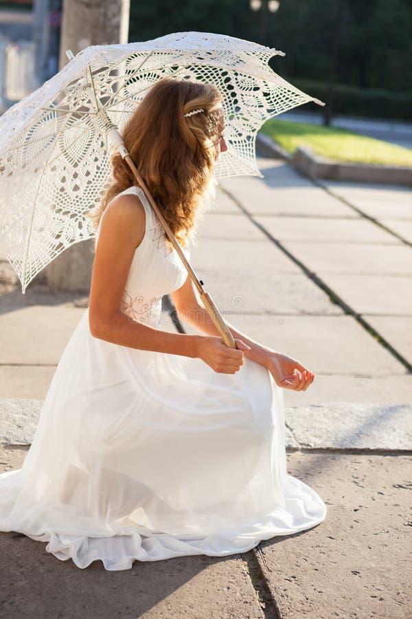 Bella sposa della ragazza con l'ombrello decorativo nel morni soleggiato fotografia stock libera da diritti