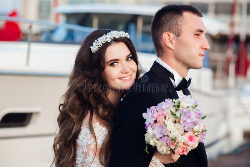 Bella sposa e sposo che abbracciano vicino all'yacht del mare fotografia stock libera da diritti