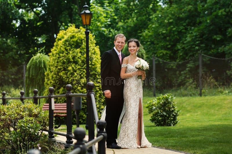 Bella sposa e sposo delle coppie felici della persona appena sposata che posano nel parco o immagine stock libera da diritti