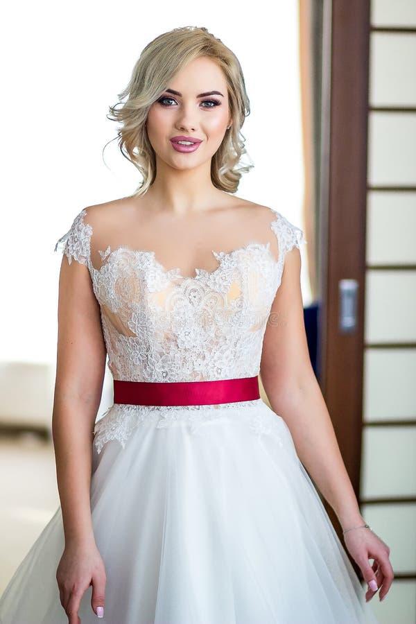 Bella sposa elegante bionda con trucco di nozze e l'acconciatura lunga che si siedono in poltrona d'annata immagini stock libere da diritti