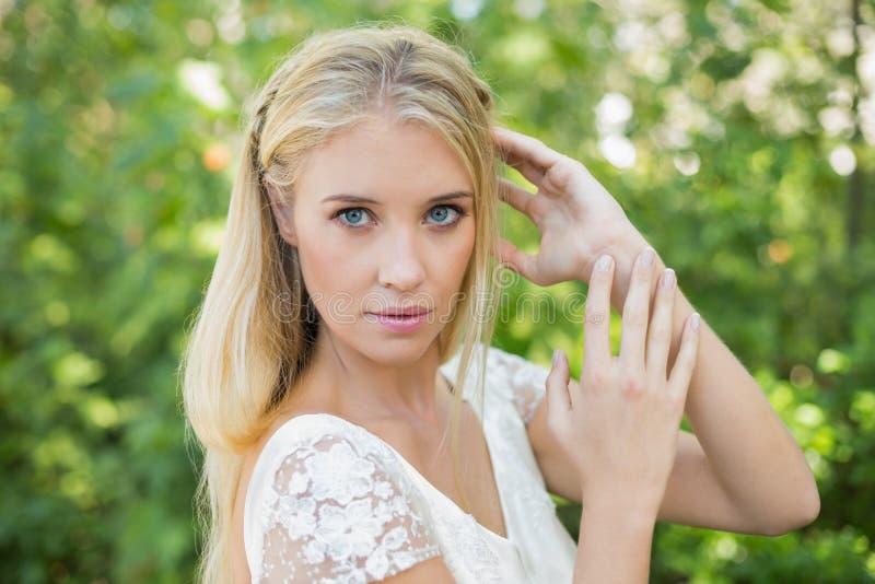 Bella sposa felice che tocca i suoi capelli fotografia stock libera da diritti