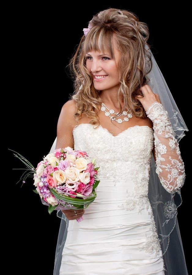 Bella sposa felice su fondo nero con il mazzo di weddin immagine stock