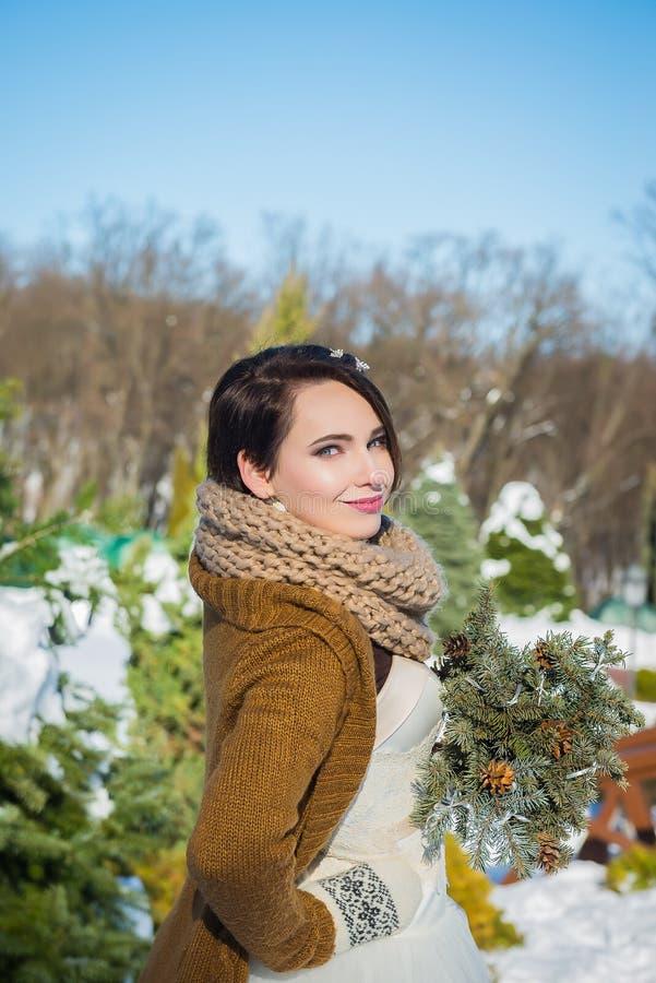 Bella sposa felice in un giorno di inverno nevoso tempo soleggiato stylish con il mazzo di nozze reso dal pino fatto a mano mitte immagini stock
