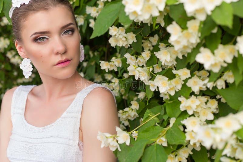 Bella sposa graziosa delicata sexy della ragazza in un vestito bianco, con trucco delicato e capelli, con gli orecchini fatti dai fotografia stock libera da diritti
