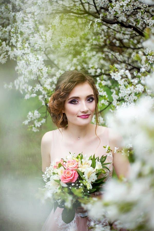 Bella sposa nel mazzo della tenuta del vestito da sposa in mani fotografia stock