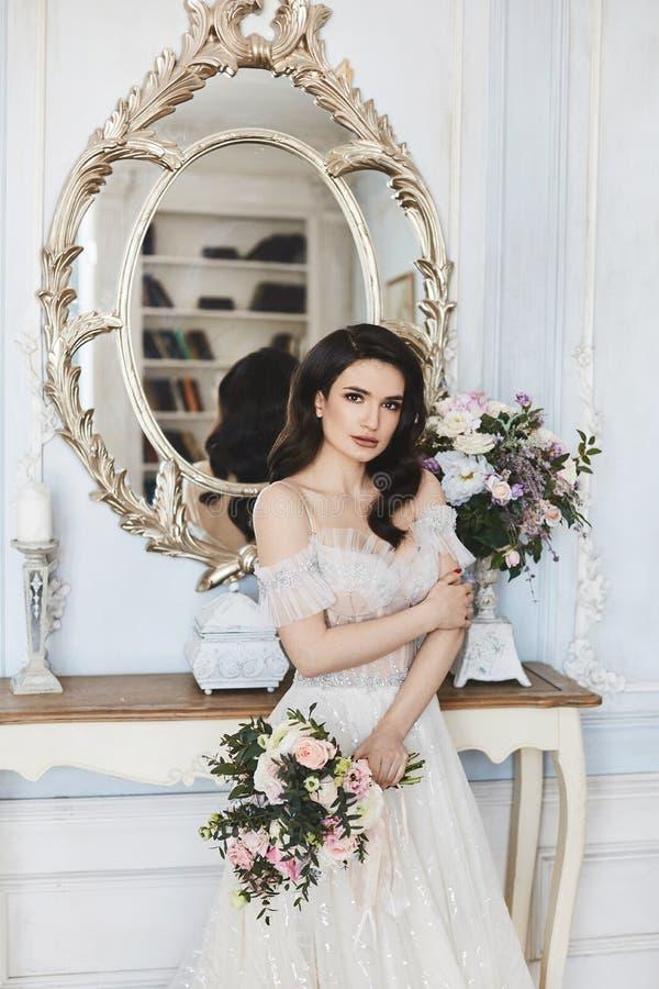 Bella sposa, ragazza castana di modello affascinante in vestito alla moda dal pizzo di nozze con le spalle nude e spirito un mazz immagini stock libere da diritti