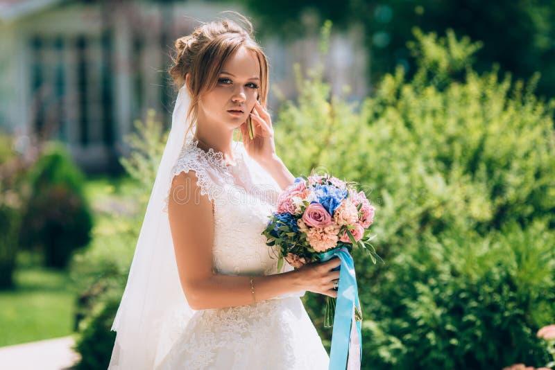 Bella sposa snella che posa contro la pianta nel parco È vestita in un bello vestito da sposa bianco, dentro fotografia stock libera da diritti
