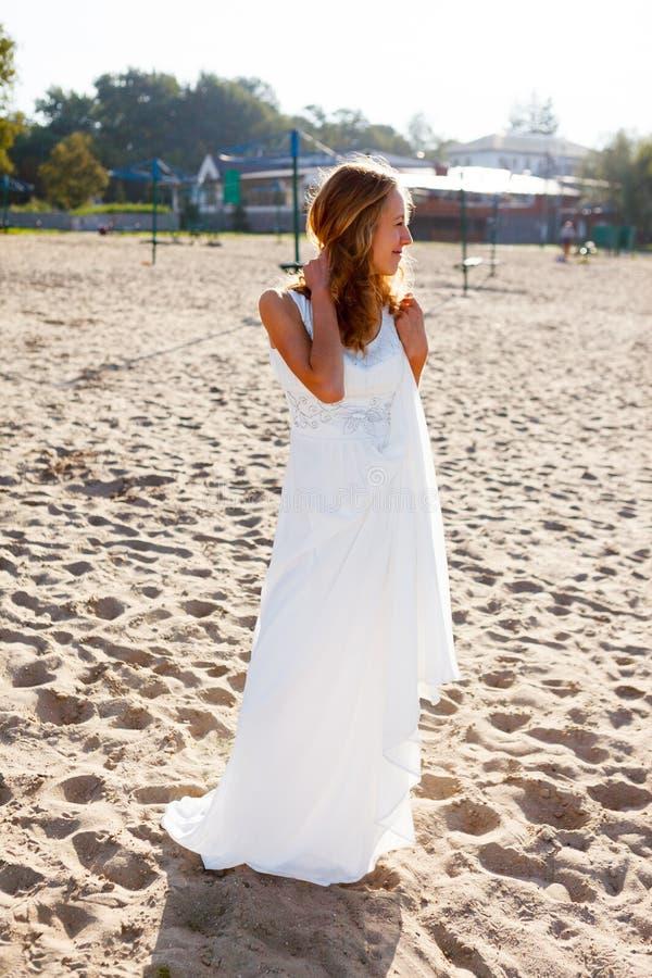 Bella sposa sorridente della ragazza in un vestito bianco sulla spiaggia soleggiata immagini stock