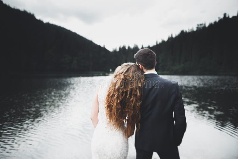 Bella sposa splendida che posa per governare e che si diverte, cerimonia di lusso alle montagne con la vista stupefacente, spazio fotografia stock libera da diritti