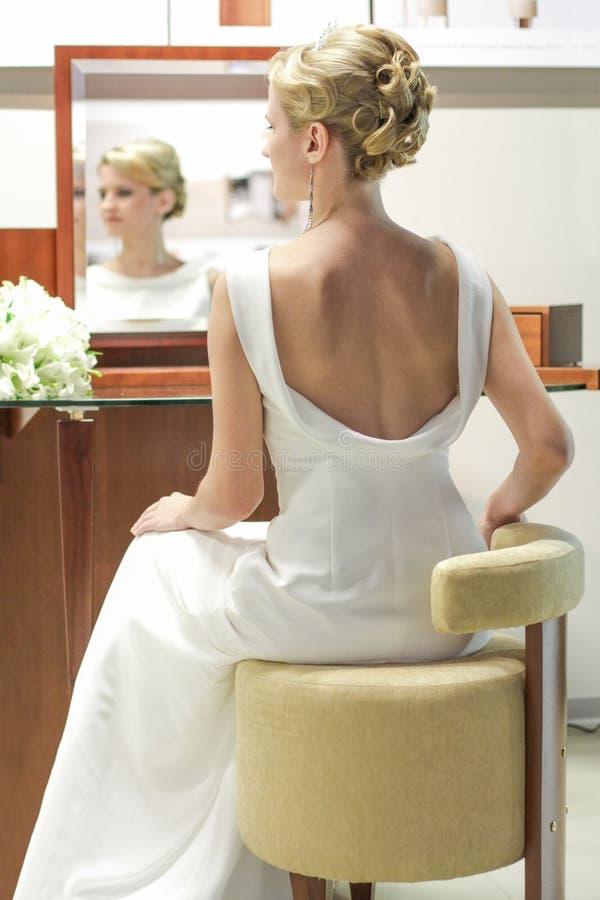 Bella sposa in un vestito da sposa ad uno specchio La ragazza prepara l'acconciatura ed il trucco fotografia stock libera da diritti