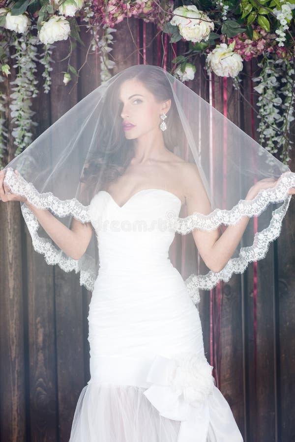 Bella sposa in un vestito da sposa con le spalle ed il velo nudi fotografie stock libere da diritti