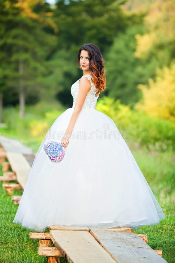 Bella sposa in vestito da sposa ed in mazzo nuziale, felici recentemente fotografia stock libera da diritti