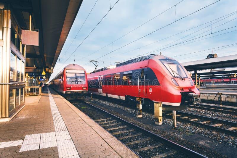 Bella stazione ferroviaria con i treni pendolari rossi ad alta velocità moderni immagine stock