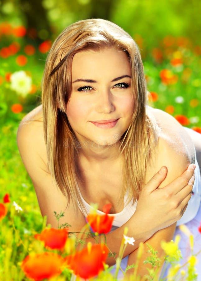 Bella stenditura femminile sul giacimento di fiore fotografie stock libere da diritti
