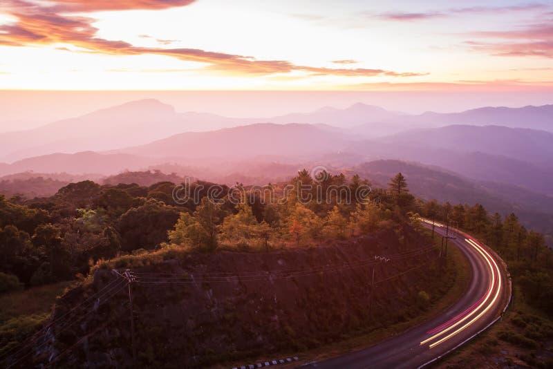 Bella strada ad alba, strada asfaltata della montagna della curva con la traccia leggera dai fari che conducono attraverso la cat fotografia stock libera da diritti