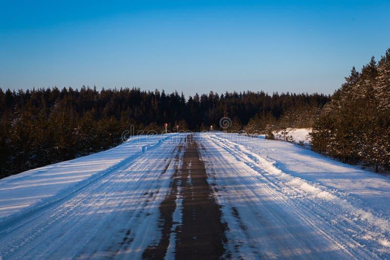 Bella strada di inverno attraverso i campi, il tramonto e le foreste nevosi immagine stock libera da diritti