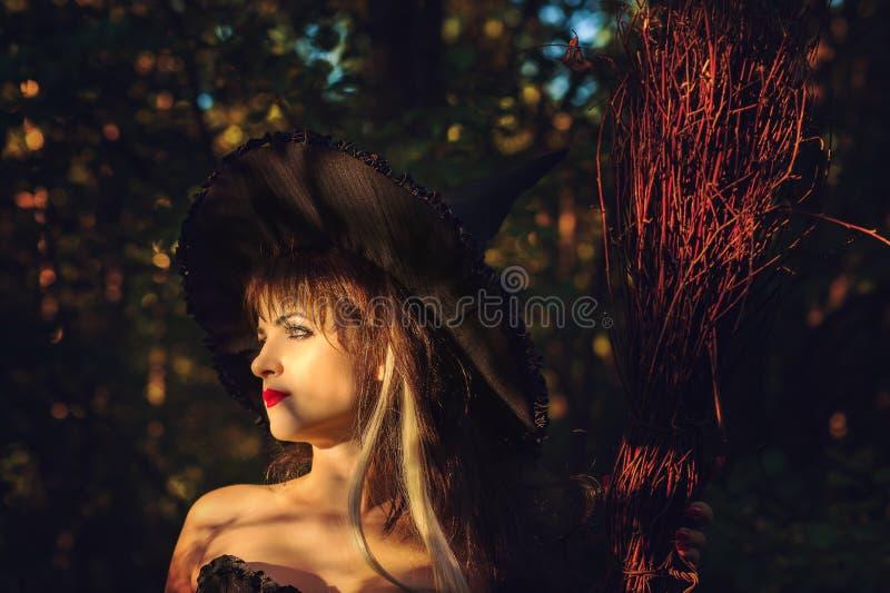 Bella strega della donna con il cappello e la scopa immagini stock