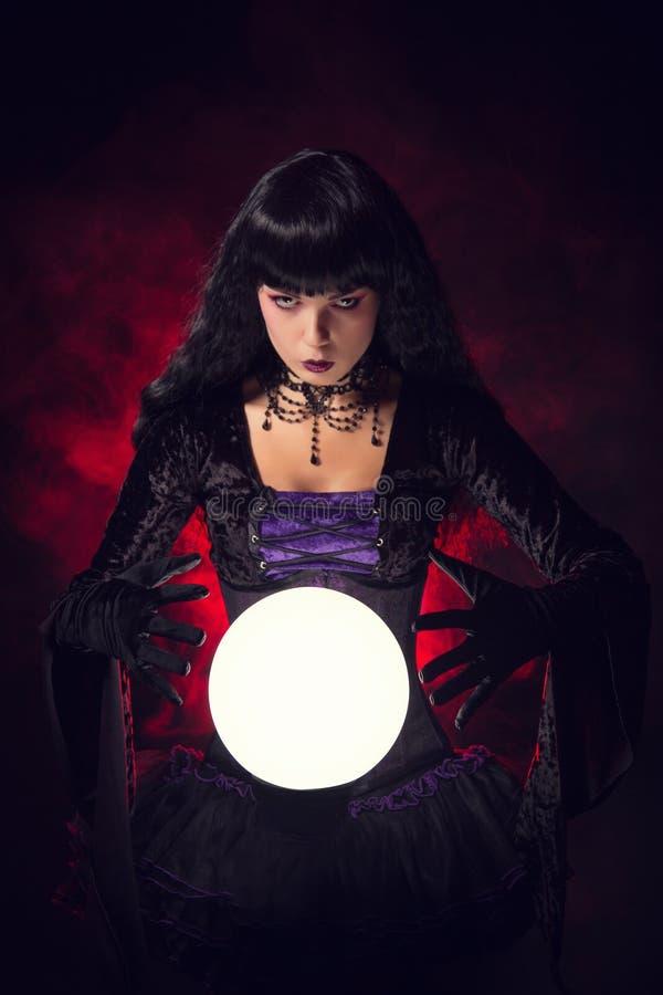 Bella strega o indovino con una sfera di cristallo fotografia stock libera da diritti