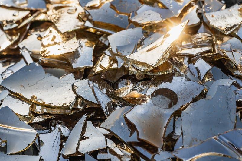 Bella struttura del vetro colorato rotto nei piccoli pezzi taglienti con acqua sul tramonto arancio con cielo blu ed il sole gial immagini stock