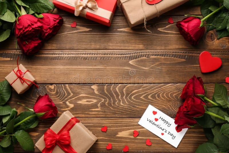 Bella struttura fatta con le rose rosse ed i regali sulla tavola di legno Celebrazione di giorno di biglietti di S. Valentino fotografie stock