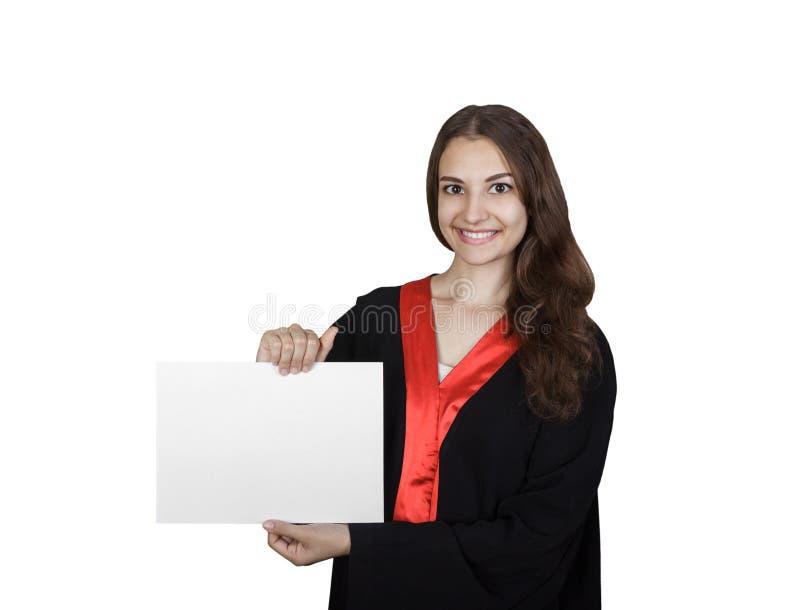 Bella studentessa laureata in manto che mostra il bordo in bianco del cartello, isolato su fondo bianco fotografia stock