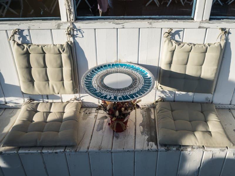 Bella tavola rotonda con i cuscini molli per un sedile in un caff? Russia della via in Soci immagine stock